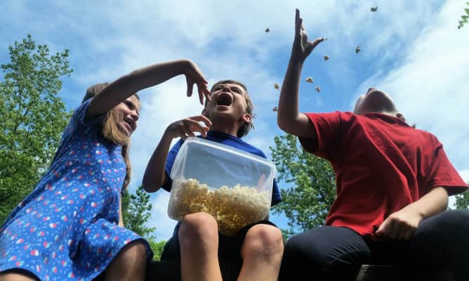 Kids being kids throwing popcorn in air and catching the kernels in their mouths as only Gen z kids can do having fun outdoors eating a snack.