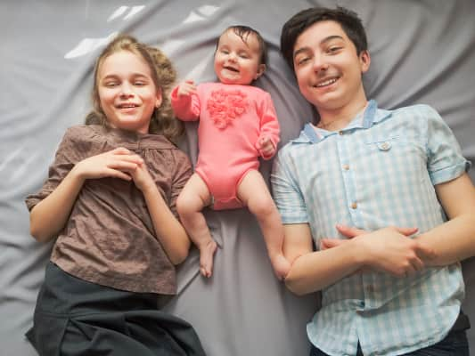 Happy family. Children playing with her little sister laying on bed laughing looking after baby