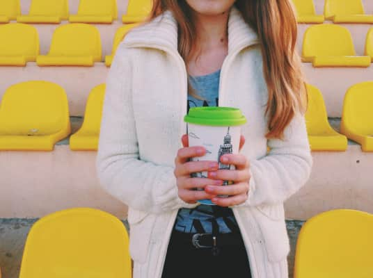 A girl in a sweater holds a mug against the background of yellow seats