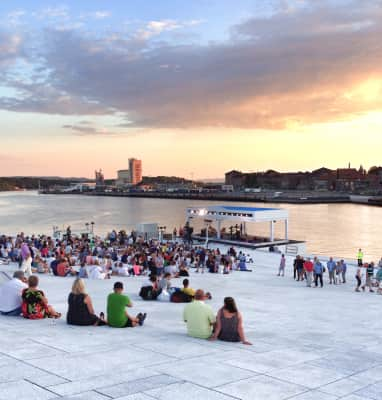 People attending a show near a harbour before sunset, waterfront, cityscape, evening light, sunset, copy space
