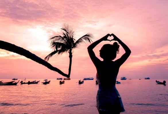 Heart shaped silhouette woman made with hand standing by sea and silhouette coconut tree