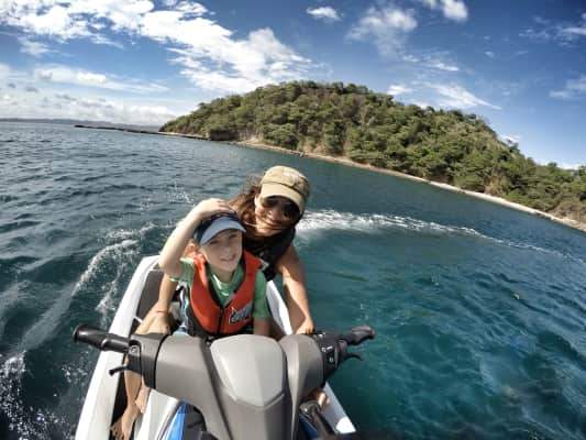 Mother and Son jet skiing in ocean