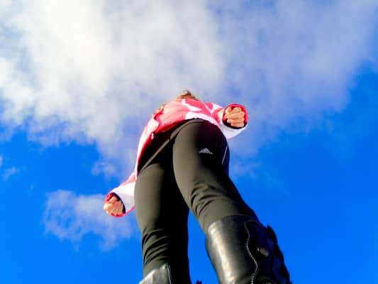 Looking up at young woman wearing winter clothes standing under the clear blue sky