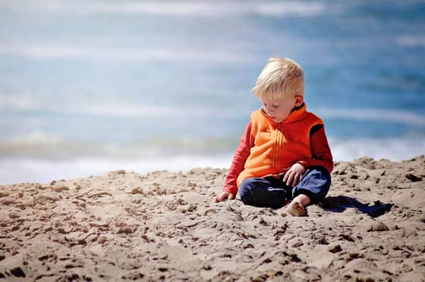 Little boy sitting on the beach with his hands in the sand