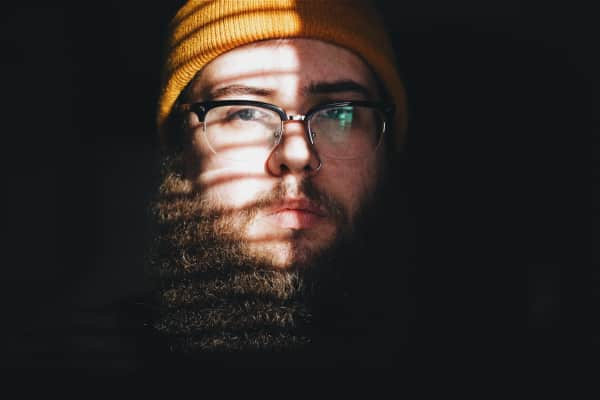 Moody portrait of glasses wearing bearded hipster