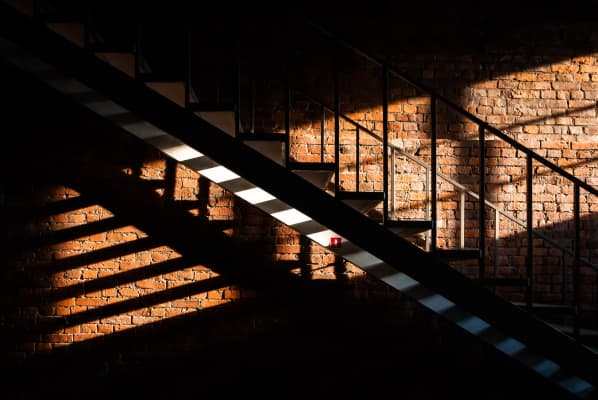 light from the window on the stairs on the background of a brick wall