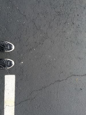 Black and white picture of shoes on the tennis court