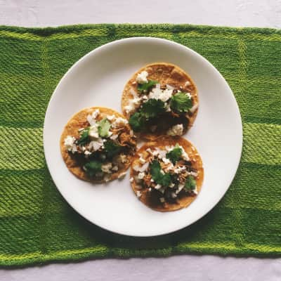 Tacos on white plate on green placemat.