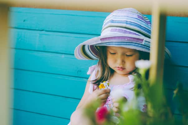 A girl in a purple hat and a summer sundress is sitting on a bench and playing with flowers in summer