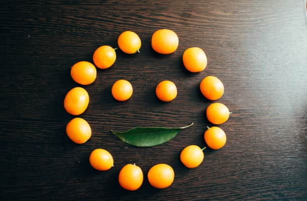 On the dark wooden surface there are orange small round fruits in the shape of a face and a smile