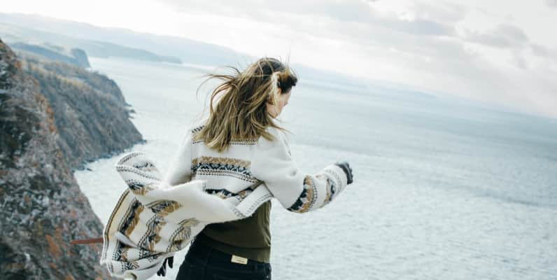 The girl stands with her back on the edge of the cliff and looks down at the sea, her hair fluttering in the wind