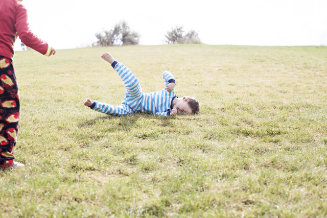 boy rolling down a hill in his pajamas