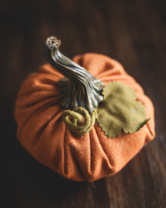 A burlap pumpkin sits on a brown table on the first day of fall.