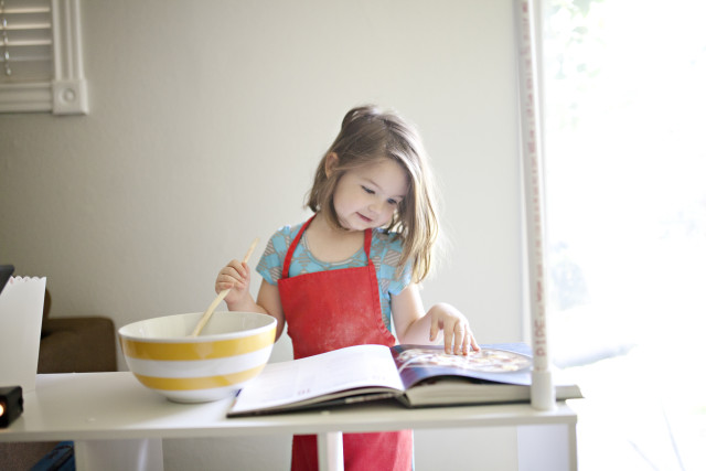 young girl playing pretend baker in a playroom at home