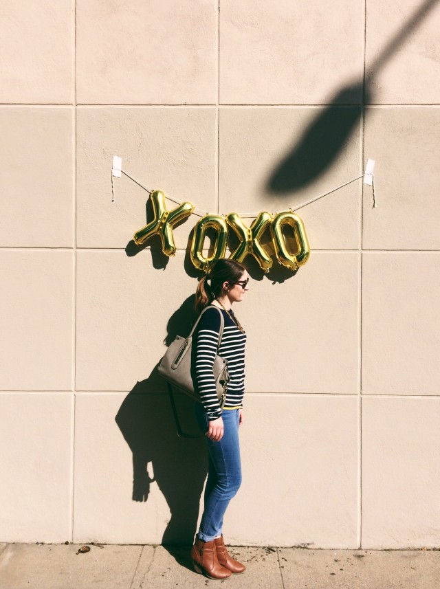 Young woman standing on the sidewalk under a balloon.