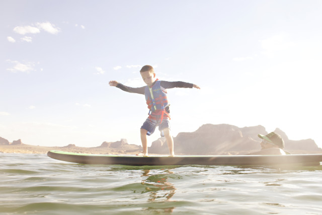 father and son at a lake on a surfboard paddle board
