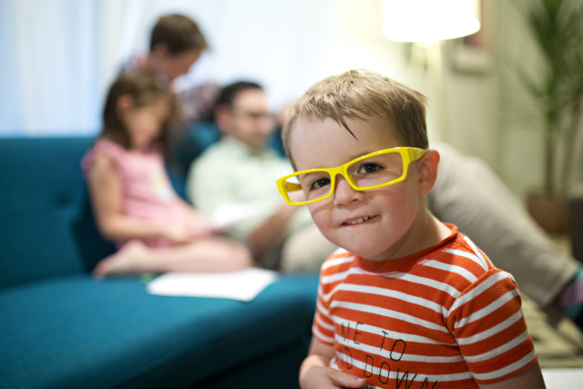 Little boy in yellow glasses being cute while family reads books in background