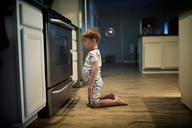 boy waiting by the oven for the cookies to bake