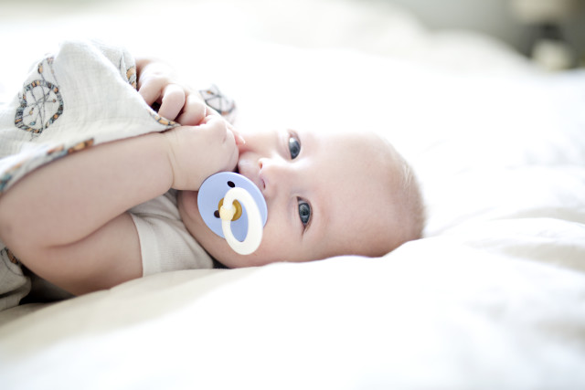 Newborn baby boy lying on a white bed