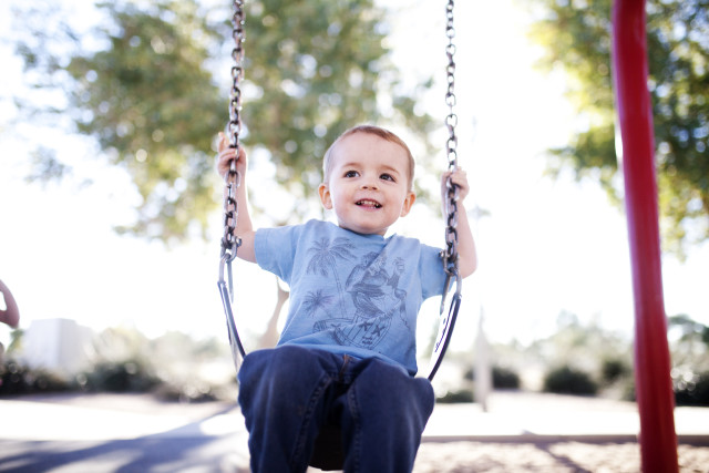 Toddler on a swing in the park