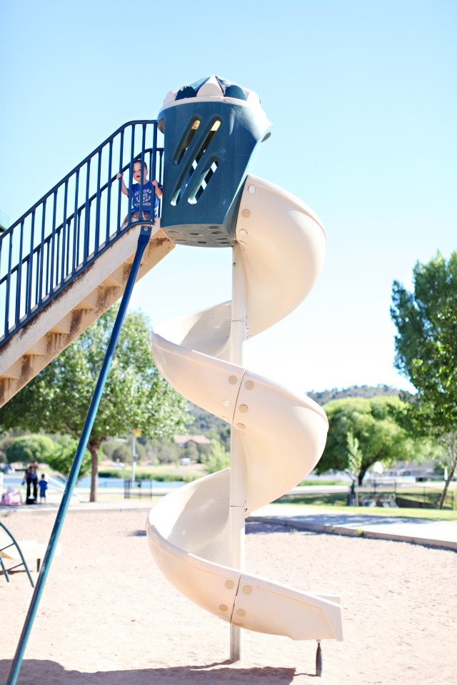 Boy atop a tall slide at the playground.