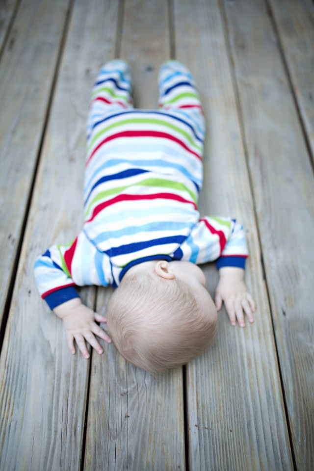 Baby sleeping on a park bench