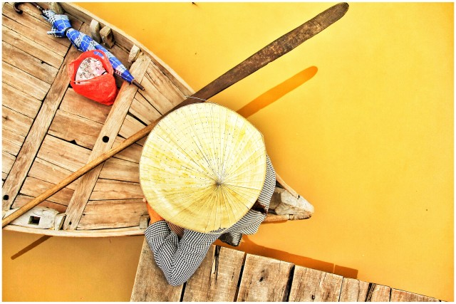 Woman with Vietnamese hat sitting in a boat in Hoi An, Vietnam
