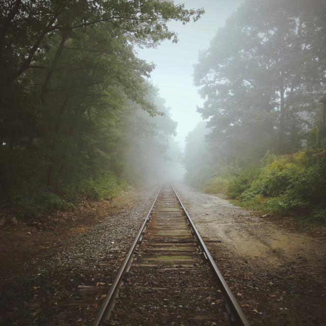 Railroad track vanishing into fog