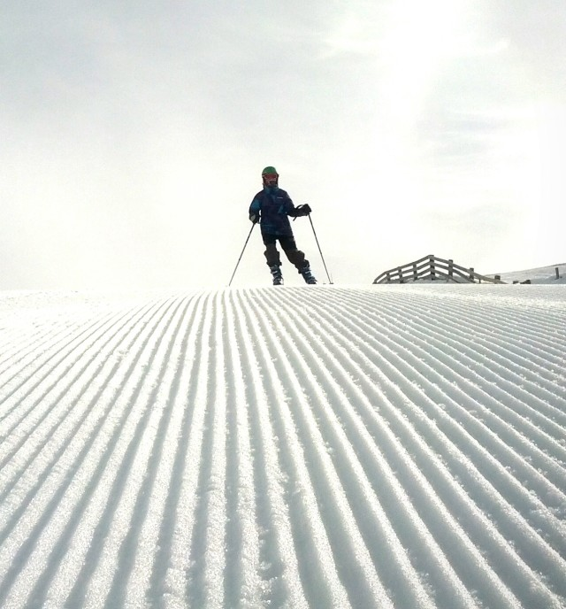 Skier on a manicured slope
