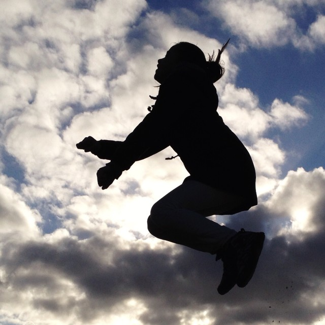 Jumping girl, shot from below, in silhouette.