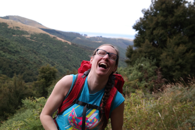 A backpack wearing woman centered in the shot, with glasses and braided hair, with eyes closed and laughing in front of a tree and vegetation filled valley leading to the ocean.
