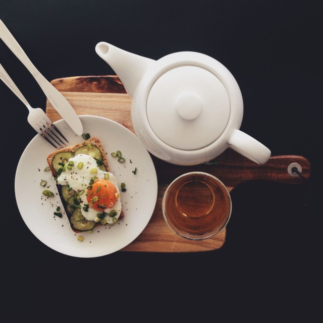 A healthy breakfast scene for one against a black background. Poached eggs on toast with cucumber and a pot of tea on a wooden serving board.
