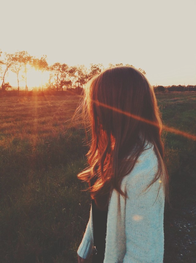 The girl looks at the sunset