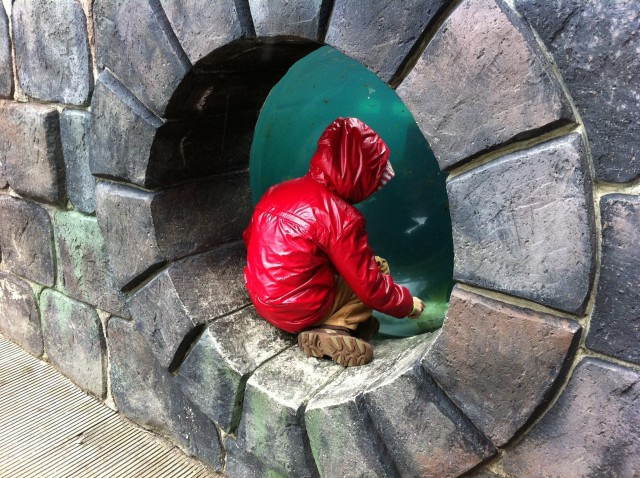 Child in round stone window with red raincoat