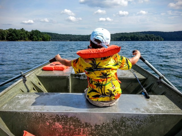 A boy in an aloha shirt rows a boat across Loch Raven Resevoir near Baltimore Maryland
