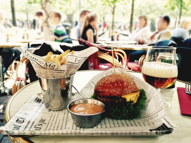 Burger, fries and beer on the table of restaurant's summer terrace.
