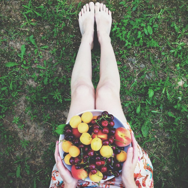 Hands holding a plate of tropical fruit