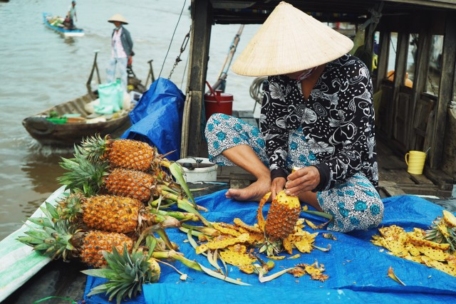 Carving pineapple at a floating market.