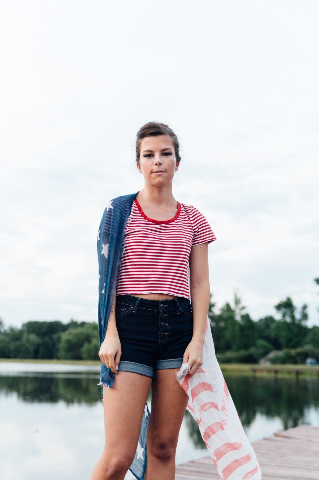 Young woman standing on a lake dock draped in an American flag scarf.