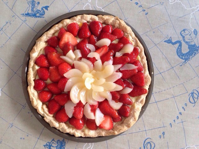 Home-made strawberry and pear tart on the table from above