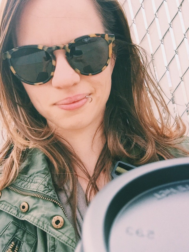 Selfie of a young woman wearing sunglasses holding a cup of coffee.