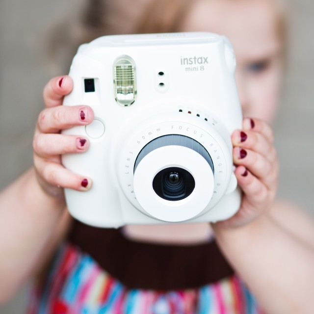 Little girl behind a white instax mini 8 instant camera.