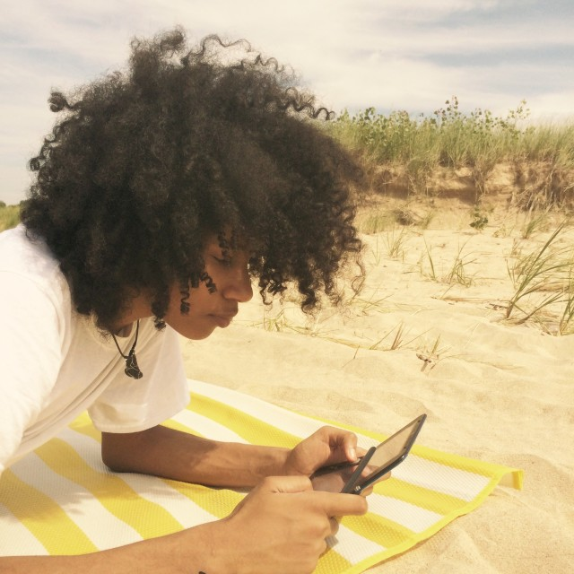 Teenager on his device at the beach