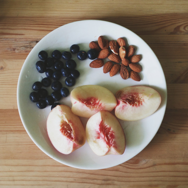 Peaches, almonds and blueberries on a plate shot from above