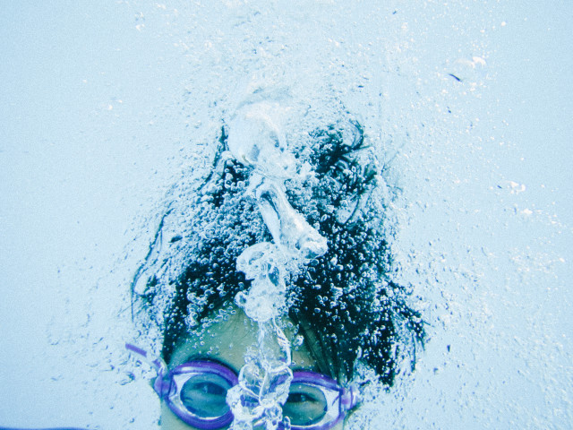 Asian girl swimming underwater exhaling air with lots of bubbles