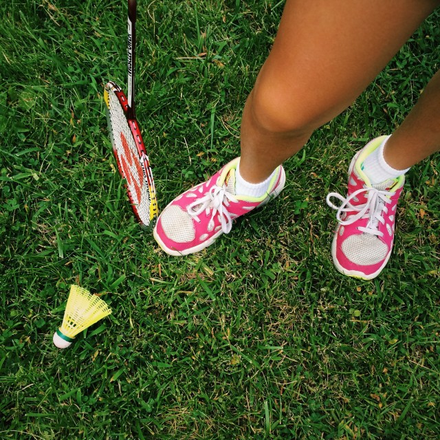 Girl badminton player standing on grass