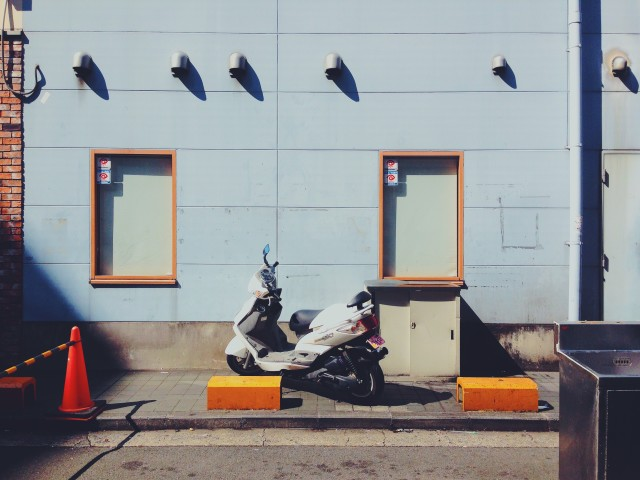 A lonely moped in front of a pretty blue wall in Yokohama.