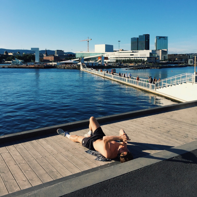 Young adult lying on a deck alongside the bay, summertime, in a contemporary cityscape environment