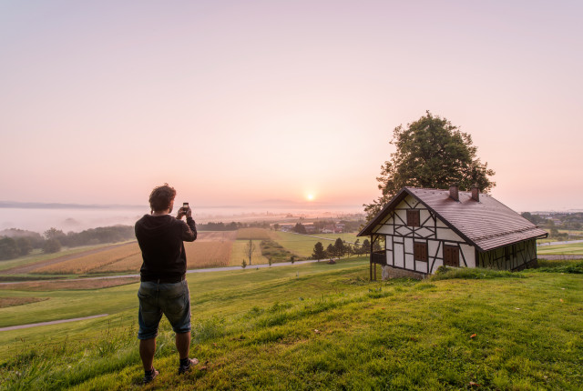 Beautiful sunrise by the medieval house in rural countryside of Slovenia. Self portrait :)