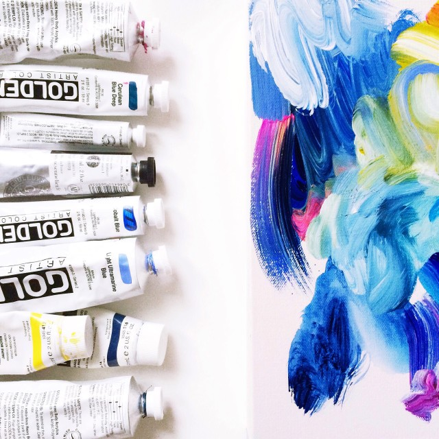 Row of paint tubes lined up next to work in progress on white background.